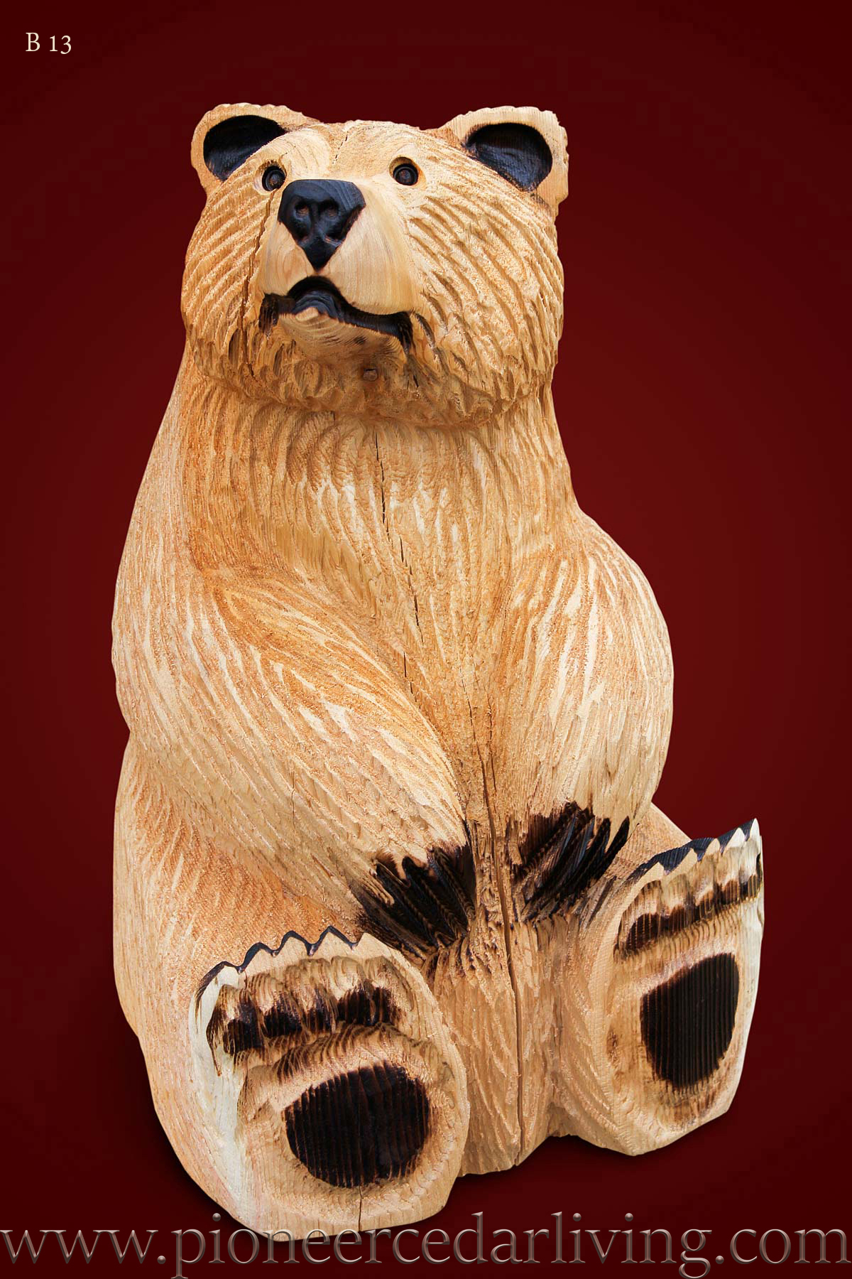 Chainsaw carving of a sitting bear pioneer cedar living